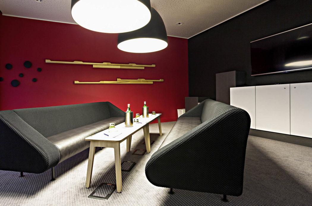 Salon avec banquette et mur rouge au Novotel Milano Linate Aeroporto